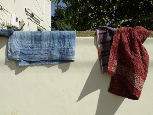 Ajrakh quilts hanging on the wall outside Ismail's house. Photo: Ruth Clifford