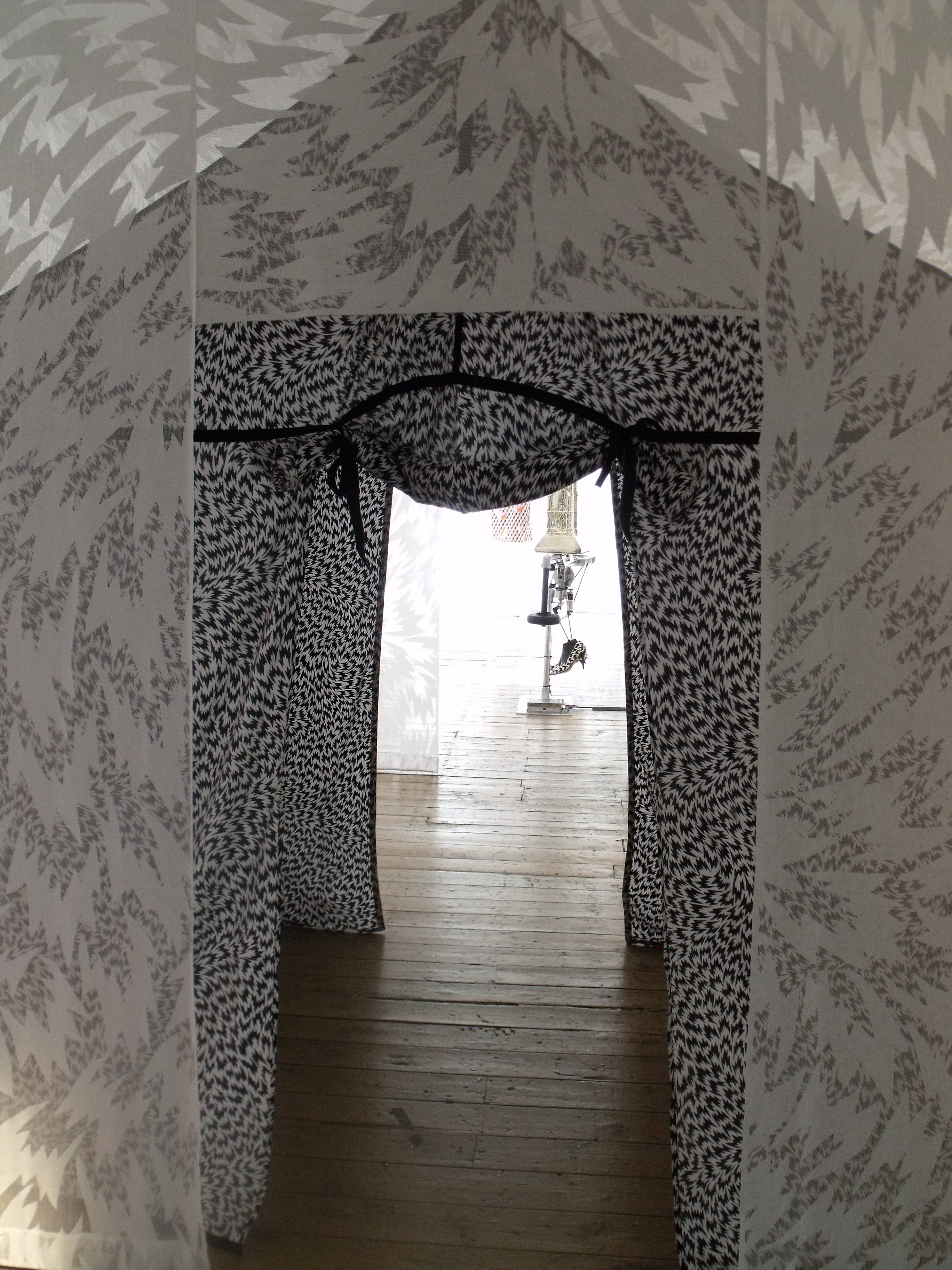 The beginning of the exhibition - a series of doorways through a monochrome patterned tent-like structure. photo: Ruth Clifford