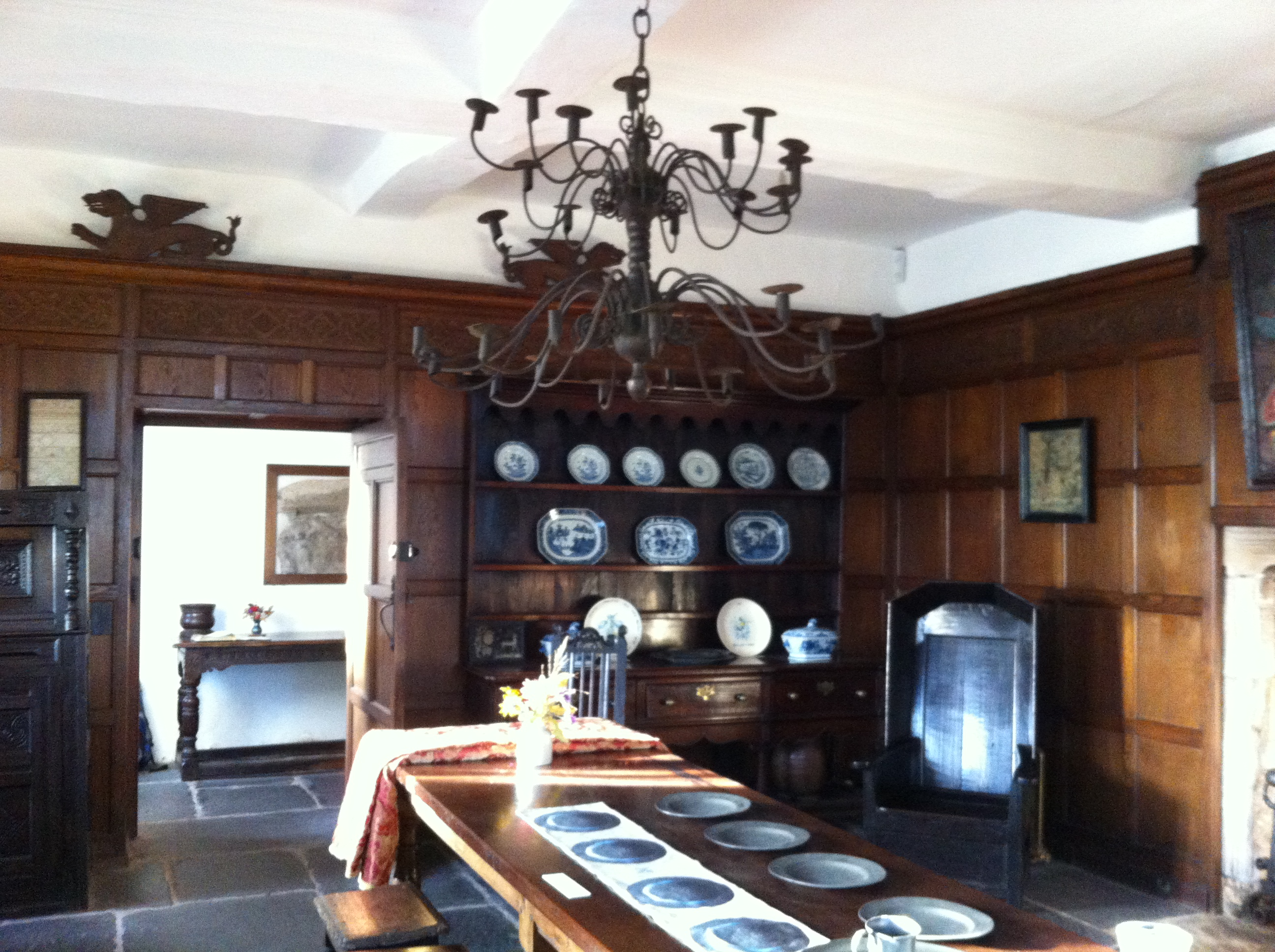 The dining room of Swarthmoor Hall. On the table is a runner with digitally printed plates mirroring the real plates on the table. each imprinted with quotes from the Household account book of Sarah Fell