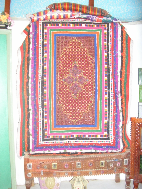 An embroidered and patchwork quilt covering a pile of quilts in a home in Dhordo, Kachchh