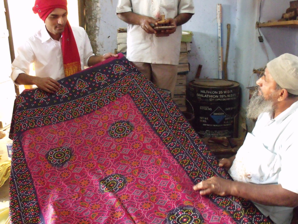 Kuldip admiring a traditional block printed women's odhini (shawl) by Kasimbhai Khatri in Khavda