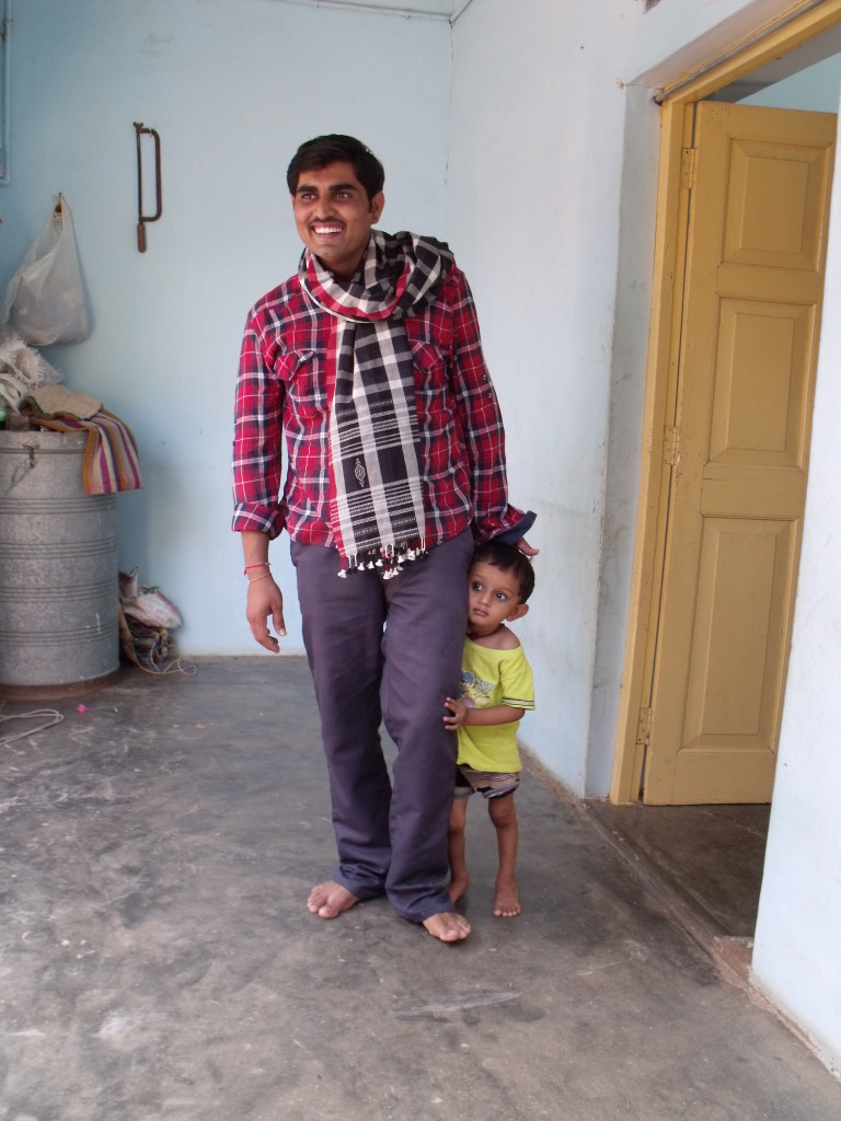 Jenti modelling a check scarf woven for the Bhujodi to Bagalkot project with his son