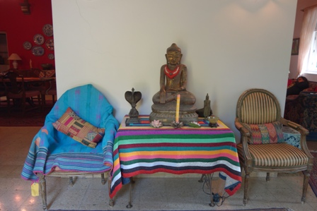 Everything is decorated in Geeta's house. Ralli quilts cover this table and chair while the Buddha statue wears a garland