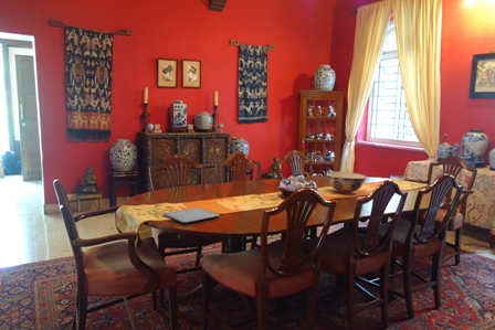 Dining room - the vivid red walls provide a complimentary backdrop to the beautiful South East Asian textiles on the walls