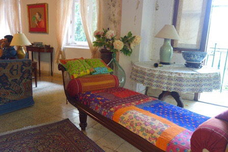 Chaise long decorated with a quilt from Pakistan and embroidered and appliqued bolster and cushions