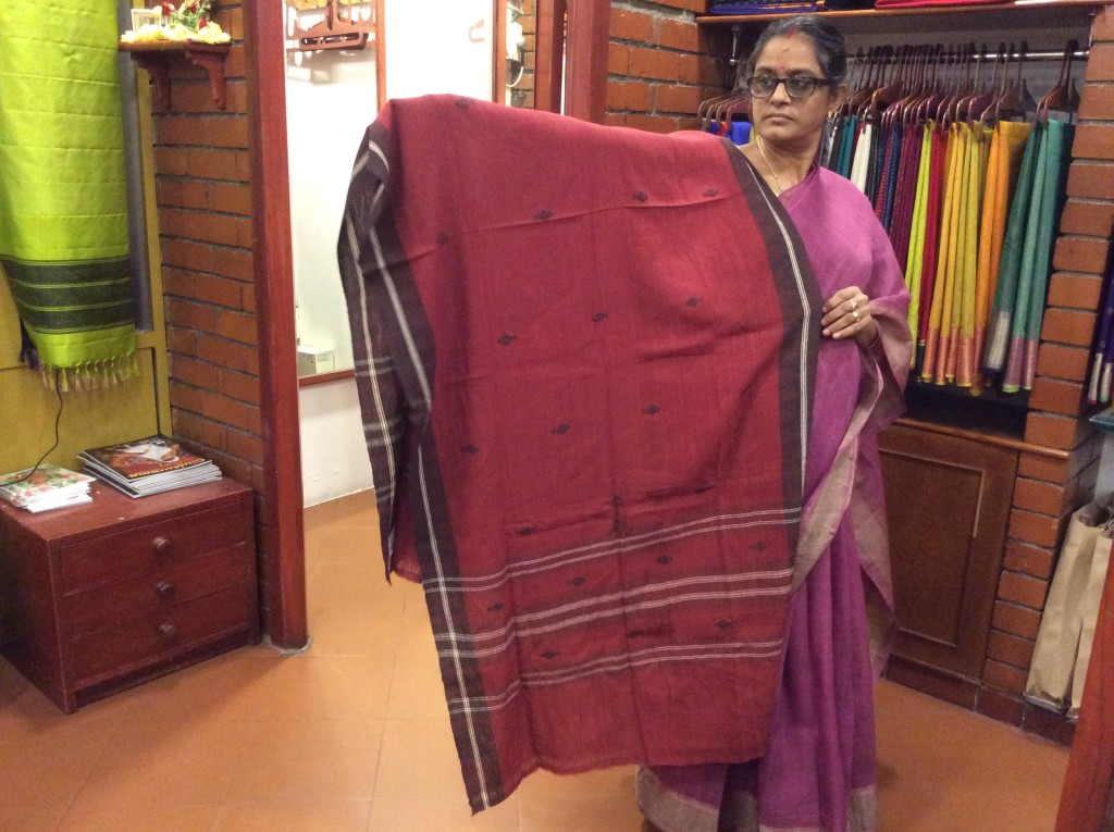 A shop assistant in Shilpi showing me a dupatta woven by a tribal community in Madhya Pradesh and dyed in natural dyes