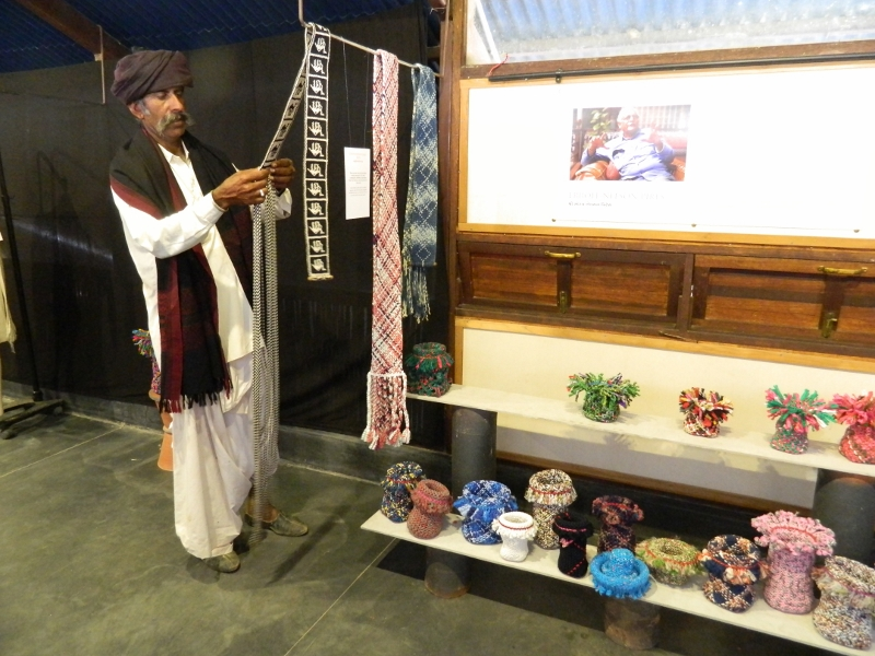 A camel herder examining one of the camel belts in the exhibition